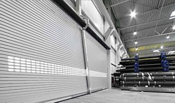 very wide insulated roller shutter door with wind protection system installed